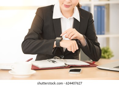 asian smiling businesswoman using her wrist news smartwatch application on daily light office work space with new modern technology connection working at studio.