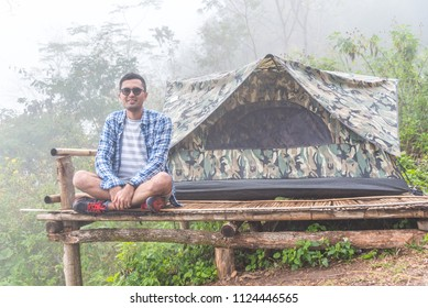 Asian smiling guy sitting on the floor in front of a camouflage tent with forest mountain view and morning fog