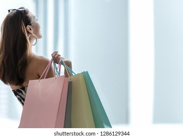 Asian smiling lifestyle woman so happy shopping in casual clothing with shopping bags in the model tower shopping mall. Lifestyle Concept.
