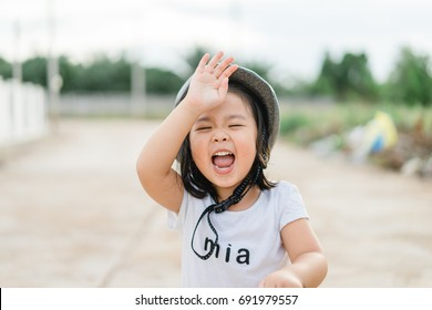 Asian smiling little girl portrait on street.Little asian girl ride scooter and wear helmet in the street.Sport girl laughing healthcare and happy life concept.