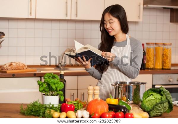 Femme souriante asiatique regardant un livre de cuisine debout dans sa cuisine