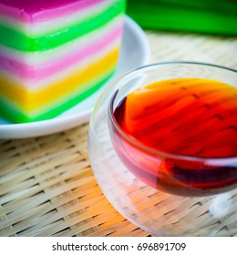 Asian snack, sweet layer steam cake with a transparent round  cup of tea background