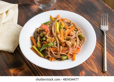 Asian Soba buckwheat noodles with vegetables and chicken, top view