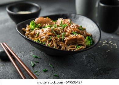 asian soba noodle and teriyaki salmon  in black bowl, selective focus
