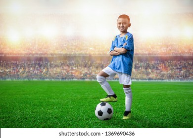 asian soccer kids player foot on the soccer ball in the stadium