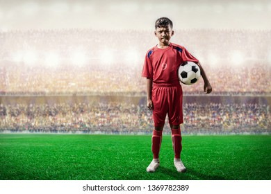 asian soccer kids player in red jersey  standing and pose to camera in the stadium