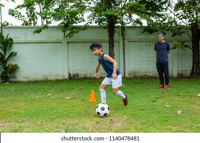 Asian soccer kids playing and trainning in the outside.