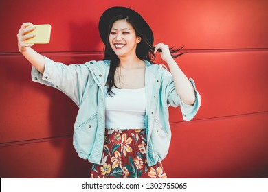 Asian social influencer woman making story for social network with smartphone camera - Happy girl having fun with new trends technology - Fashion and millennial generation activity - Focus on face