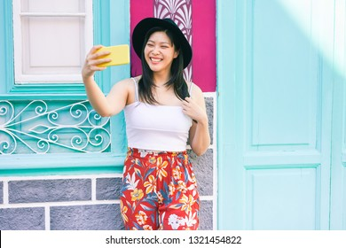 Asian social influencer woman making story for social network with smartphone camera- Happy girl having fun with new trends technology - Fashion and millennial generation activity - Focus on face