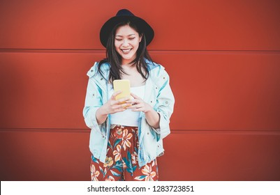 Asian social influencer woman using smartphone with coral background - Happy chinese girl having fun with new trends technology - Fashion, tech and millennial generation activity - Focus on face
