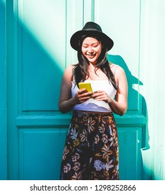 Asian social influencer woman using smartphone outdoor - Happy chinese girl having fun with new trends technology - Fashion, tech and millennial generation activity - Focus on face