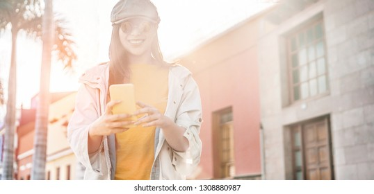 Asian social influencer woman using smartphone outdoor with back light - Happy chinese girl having fun with new trends technology - Fashion, tech and millennial generation activity - Focus on face
