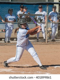 Asian softball player watching her batted ball fly.