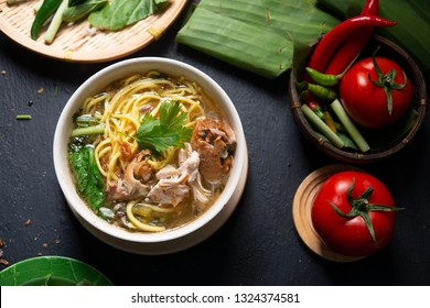 Asian soup noodles and chicken in bowl on dark background. Top view flat lay.