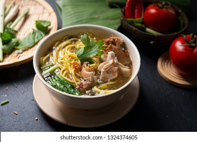 Asian soup noodles and chicken in bowl on dark background.