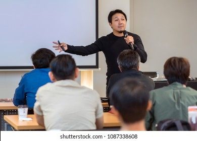 Asian Speaker with casual suit on the stage in low light over the presentation screen in the business or education seminar