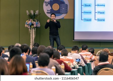 Asian Speaker with casual suit on the stage present the screen in the conference hall or seminar meeting, business and education concept