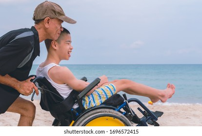 Asian special child and Father in wheelchair on the beach with daylight, They are happiness in holidays with the travel, Life in the education age of disabled children, Happy disability kid concept.