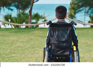 Asian special child on wheelchair is looking at sea beach, Life in the education age of disabled children, Happy disabled kid concept.