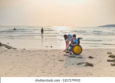 Asian special child on wheelchair and his dad on the beach at sunset, Father helped him lock the car for safety, Life in the education age of disabled children, Happy disabled kid concept.