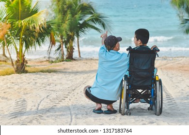 Asian special child on wheelchair is pointing at sea and his father helped him to get closer to nature, Life in the education age of disabled children, Happy disabled kid concept.