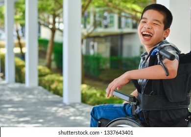 Asian special child on wheelchair is smile happily on ramp for disabled people background, Life in the education age of disabled children, Happy disabled kid concept.