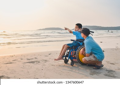 Asian special child on wheelchair and his dad on the beach at sunset, Father helped him to get closer to nature.