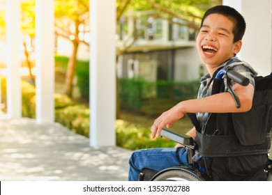 Asian special child on wheelchair is smile happily on ramp for disabled people background and orange light, Life in the education age of disabled children, Happy disabled kid concept.