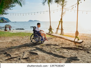 Asian special child on wheelchair is play swings on the beach, Seaside nature background, Life in the education age of disabled children, Happy disabled kid concept.