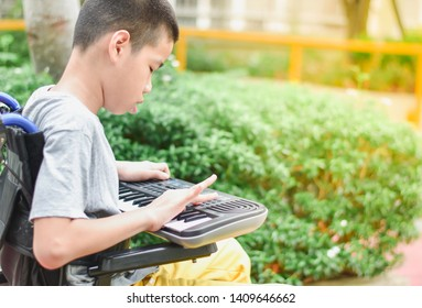 Asian special child on wheelchair is playing Mini Keyboards happily on the playground, nature background, Life in the education age of disabled children, Happy disabled kid concept.