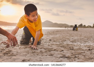 Asian special child on wheelchair is crawl on the beach at sunset, Boy play fun with adult taking care beside them, Life in the education age of disabled children, Happy disabled kid concept.