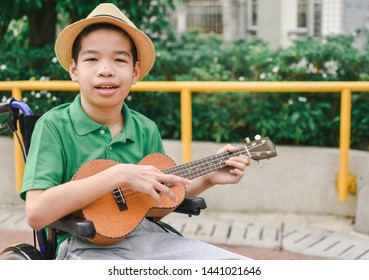 Asian special child on wheelchair is playing ukulele happily on the playground, nature background, Life in the education age of disabled children, Happy disabled kid concept.