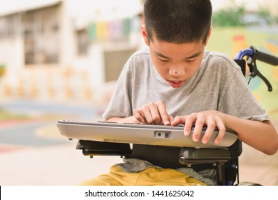 Asian special child on wheelchair is playing Mini Keyboards happily on the playground, nature background and sun light, Life in the education age of disabled children, Happy disabled kid concept.