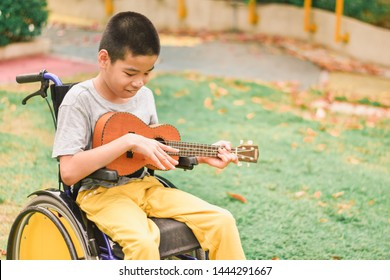 Asian special child on wheelchair is playing ukulele happily on the playground, nature background and sun light, Life in the education age of disabled children, Happy disabled kid concept.