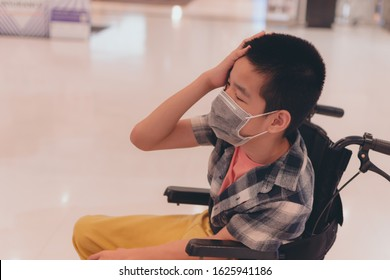 Asian special child on wheelchair wearing a protection mask against PM 2.5 air pollution with pointing up in Bangkok Thailand,Life in the education age of disabled children,Happy disabled kid concept.