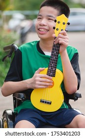 Asian special child on wheelchair is playing ukulele with happy face on the outdoor, nature background and sunset, Life in the education age of disabled children, Happy disability kid concept.