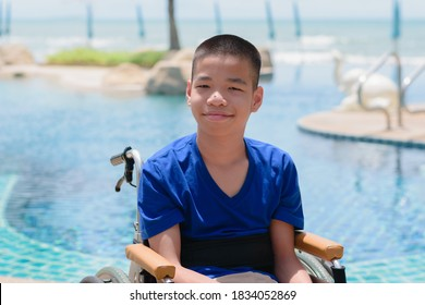Asian special child on wheelchair is smiling, playing and doing activity on the sea beach, Lifestyle of disability child, Life in the education age, Happy disabled kid in travel holidays concept.