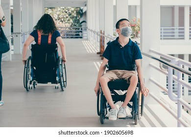 Asian special child on wheelchair wearing a protection mask against PM 2.5 air pollution and flu Covid 19 or Coronavirus on public path background, N95 to prevent the spread of the virus disease 2021.