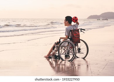 Asian special child on wheelchair is fun, playing ball and exercise activity on sea beach at summer, Lifestyle of disability child, Life in the education age, Happy disabled kid in travel concept.