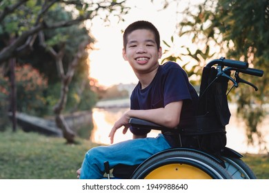 Asian special child on wheelchair is smiling face as happiness on the outdoor nature park background with parent in travel,Lifestyle in education age of disabled children,Happy disability kid concept.