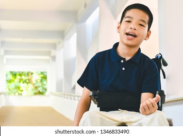 Asian special child is sitting the wheelchair and be smile, On the ramp for the disabled, Life in the education age of children, Happy cerebral palsy kid concept.