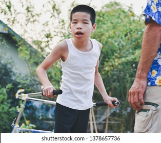 Asian special child is walking by using walker training equipment, Life in the education age of disabled children, Happy disabled kid concept.
