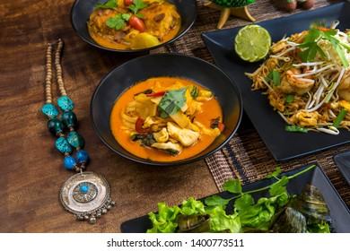 Asian specialties, assortment of several recipes of Thai cuisine, served on a wooden table