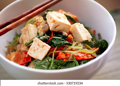 Asian spicy stir fry vegetable with tofu and beans in white bowl and chopsticks closeup