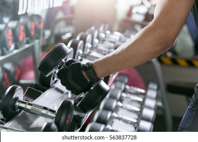 Asian sport man doing one-arm dumbbell rows of metal in modern gym.