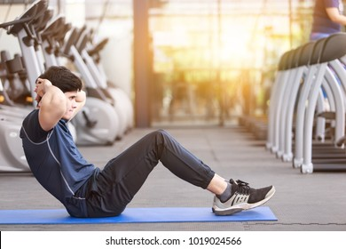 Asian sport man doing sit-ups on the floor in gym. man exercising in fitness gym for good health. Athletic young man exercising equipment at gym, workout in fitness center.