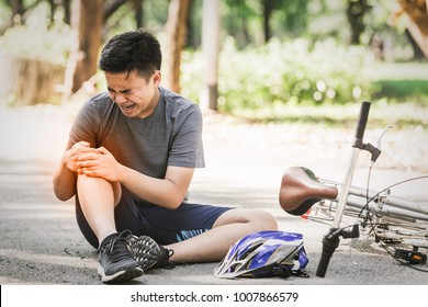 Asian sport young man cyclist riding mountain bike accident spin down and fall knee injured on road. Sport life healthy concept in the summer