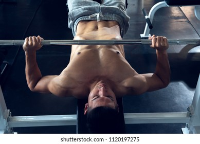 Asian sports young man doing exercises with barbell on bench in the sport gym,  Bench Press machine equipment bodybuilder concept.