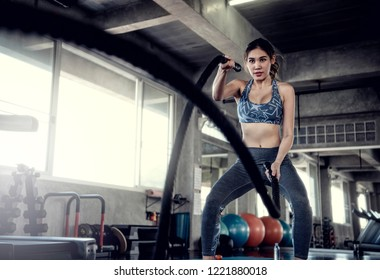 Asian sportswoman fit training with battle rope in fitness gym. Sport and workout motivation concept.
