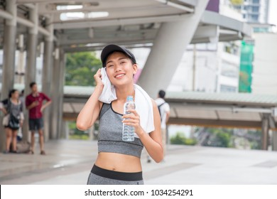 Asian sporty woman is holding a bottle of still water during exercise
